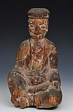 A CHINESE CARVED BUDDHA with traces of polychrome decoration, late Ming, 31.5cm high