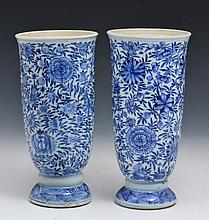 A PAIR OF CHINESE BLUE AND WHITE EXPORT TYPE BEAKER VASES on upturned saucer style bases, decorated