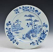 A CHINESE BLUE AND WHITE PORCELAIN PLATE decorated with a pagoda and a house amidst rocks on an isla