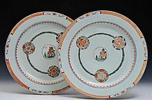 A PAIR OF CHINESE EXPORT PORCELAIN CHARGERS with famille rose decoration showing a central landscape
