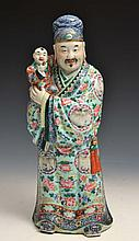 A CHINESE PORCELAIN FIGURE OF A WU TI'S COURTIER carrying Wu-Ti's heir Fu-lin decorated in famille rose enamels