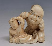 A JAPANESE OKIMONO of a father playing with his child and holding a Noh mask to his face, Meiji