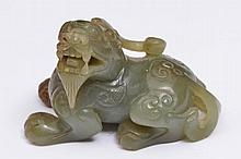 A CHINESE JADE CARVED TEMPLE DOG with head turned to the side, 18th/19th Century, 7cm across