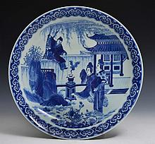 A CHINESE BLUE AND WHITE PORCELAIN CHARGER, young boy climbing over a wall with two ladies in a gard