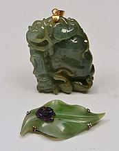 A CHINESE GREEN CARVED JADE PENDANT with gilt
