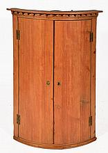 A REGENCY STRIPPED PINE BOW FRONTED HANGING CORNE
