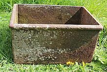 A SMALL RECTANGULAR CAST IRON WATER TROUGH OR PLA