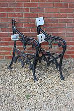 A PAIR OF OLD BLACK PAINTED CAST IRON BENCH ENDS