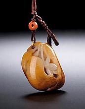 A WHITE AND RUSSET JADE LOTUS PENDANT