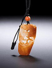 A WHITE AND RUSSET JADE 'SQUIRREL AND GRAPES' PENDANT