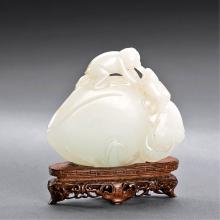 A CHINESE WHITE JADE 'MONKEY AND PEACH' CARVING