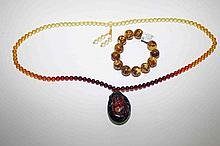 AN AMBER TYPE BEAD NECKLACE, with pendant and a