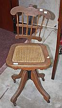 AN OAK SWIVEL DESK CHAIR, with adjustable railed back and cane seat on quat