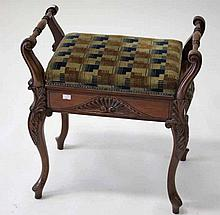 AN EDWARDIAN WALNUT PIANO STOOL,  with turned handles and a lift up sea