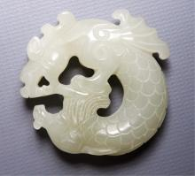 A CHINESE JADE (POSSIBLY JADEITE) BI-DISK WITH DOUBLE-SIDED CARVED THE CHI DRAGON. Z035.