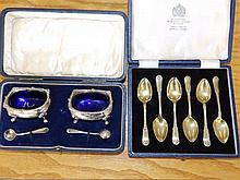 A cased pair of silver mustards with spoons and a cased coffee spoon set