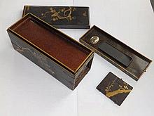 """A Japanese black lacquered calligrapher's box, decorated with a nightingale perched on prunus blossom, the top lifting to reveal a loose tray, a door to one side revealing four drawers each fitted with a white metal pounce pot and ink stone, 11"""""""