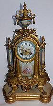 """A 19thC French eight day striking gilt spelter mantel clock with painted porcelain panels, 16"""" high, on shaped wooden base"""