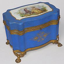A 19thC Sevres style ormolu mounted porcelain scent bottle casket, of serpentine plan, the cover decorated with a juvenile courting couple, on biscuit blue ground with gilding, the hinged cover revealing four opaque glass bottles with gilt metal
