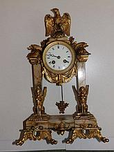 A late 19thC French ormolu mounted marble portico mantel clock in neoclassical taste, surmounted by an eagle over the circular white enamelled dial with eight day bell-striking movement, the pair of square tapering columns emerging from sphinxes, the