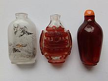 A Chinese Peking glass snuff bottle overlaid in red, together with an internally painted bottle and one other (3)