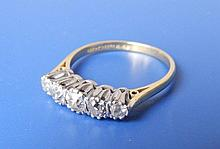 A five stone graduated diamond ring, the old cut centre stone weighing approximately .25 carat set in 18ct gold