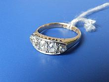 A five stone graduated diamond ring, the central old cut stone weighing approximately .50 carat in white metal setting on 18ct yellow gold shank