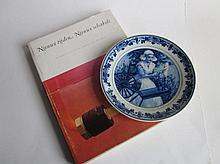Boek Algemene Kunstzijde Unie, de eerste 50 jaren van de AKU, en een Delfts AKU herdenkingsbordje, meisje met spinnewiel, aan de achterzijde gemerkt H.K.I. Breda