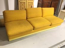 Modernist yellow upholstered armless sofa