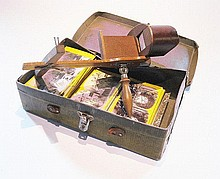 A wooden hand held stereo viewer and a box of