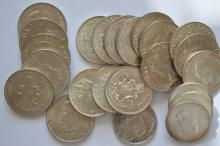 A tube of larger foreign silver coins