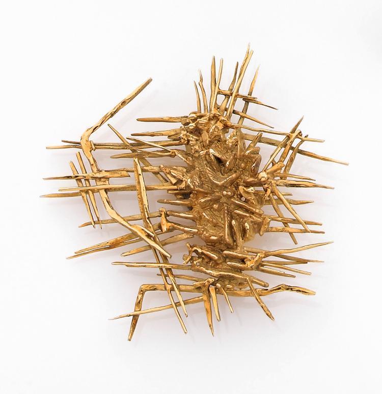 ARNALDO POMODORO Broche  en or jaune, en amas d'aiguilles entrelacées entre elles. Signée, datée 1957. Exemplaire unique.Dimensions : 6,0 x 5,4 cm environ. Poids : 23,2 g. An 18K gold brooch by Arnaldo Pomodoro, dated 1957.