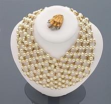 CELINE Collier draperie en résille de métal doré ponctué de perles d'imitation blanches.    Accompagné d'une petite broche patte d'ours en métal doré et strass.    Non signés