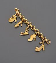 FERRAGAMO Bracelet gourmette en métal doré, orné de cinq pampilles en forme de chaussures.    Signé