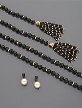 CELINE Négligé en perles de verre noir facettées, alternées de viroles en métal doré et strass, terminé par deux pompons. Accompagné d'une paire de boucles d'oreille, une pierre noire facettée retenant en pampille une perle blanche d'imitation. Non