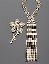 CELINE Collier cravate en métal argenté serti de strass, retombant au décolleté en lignes mobiles.    Signé    Accompagné d'une broche fleur en métal argenté et pavée de strass    (accidents) Monogrammée