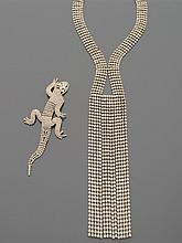 CELINE Collier cravate en métal argenté serti de strass, retombant au décolleté en lignes mobiles.    Non signé    Accompagné d'une broche lézard en métal argenté pavée de strass.    Non signée