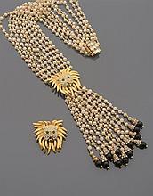 CELINE Sautoir en cinq rangs de perles d'imitation blanches, centré d'une tête de lion en métal doré et pavée de strass, retenant un pompon de douze rangs de perles d'imitation terminés par une virole pavée de strass et une perle de verre noir. Signé