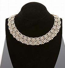 Collier collerette en métal doré, à décor de fleurs pavées de strass, agrémenté de perles rosées d'imitation en chute.