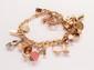 Bracelet gourmette en or jaune agrémenté de breloques en or jaune, argent et pierres dures. <br> <br> Longueur : 18 cm environ. <br> <br> Poids : 45,4 g. (14k) <br> <br> An 14K gold and silver bracelet.