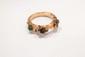 Bracelet jonc articulé en branche d'or jaune stylisée figurant trois scarabés dont deux naturalisés, le troisième en pierre dure.       Poids brut : 55,9 g. (accident)   An 18K gold bracelet.