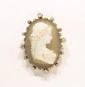 Broche camée sur agate, figurant une jeune fille de profil portant un bonnet, monté sur or jaune et piqué de petits diamants en roses.       Dimensions : 40 x 30 mm environ.       Poids : 15 g.      A diamond, agate and 18K gold cameo.