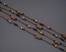 CHANEL        Sautoir en anneaux imbriqués de métal doré, des perles d'imitation alternent avec des perles de verre imitant le lapis et des perles de métal doré ajourées.     Années 1950.     Longueur : 176 cm environ.