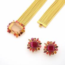 Daniel SWAROVSKI     Long collier multi-rangs en métal doré, fermé devant par une importante strass imitant une citrine dans un entourage de verre de couleurs.