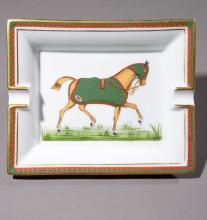 HERMES Paris Made in France     Cendrier en porcelaine à décor d'un cheval et sa tenue, liseret bicolore et or.