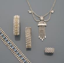 Lot comprenant:      Un collier en métal argenté à décor de draperie sertie de strass; trois bracelets en métal argenté et strass, dont un agrémenté de pierres bleues; une bague en métal argenté et strass.