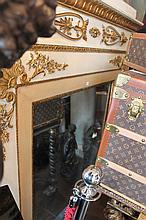 Miroir dans un encadrement en bois doré et stuqué.