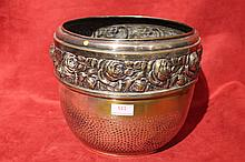 Cache-pot en métal argenté martelé orné d'une frise de roses.