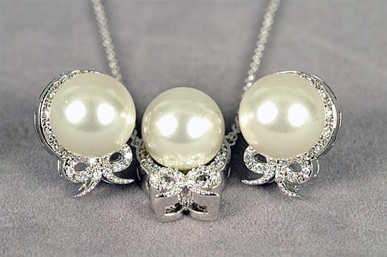 Juego de dije con cadena y par de aretes. Elaborados en metal blanco. Diseño con imitación de perla y simulantes. Peso: 10.4 grs. 2 pz.