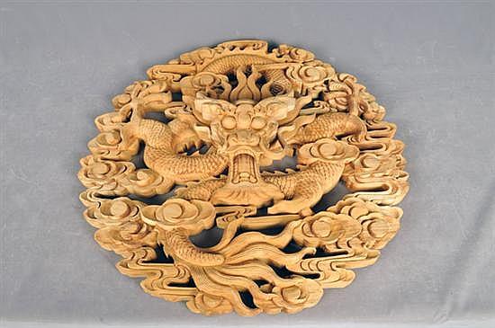 Medallón. Origen chino. Elaborado en madera tallada. Diseño calado a manera de dragón. Presenta faltante. Dimensiones: 60 cm.Ø